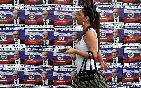 "A woman walks past posters showing Russian President Vladimir Putin reading ""Welcome, President"" in Belgrade (AFP/Getty Images)"